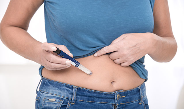 woman using autoinjector device for medication